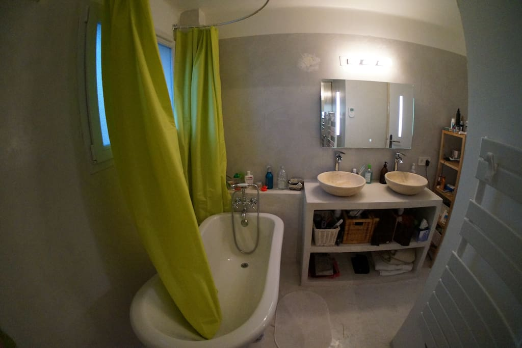 Salle de bain avec meuble en béton ciré et baignoire belle époque
