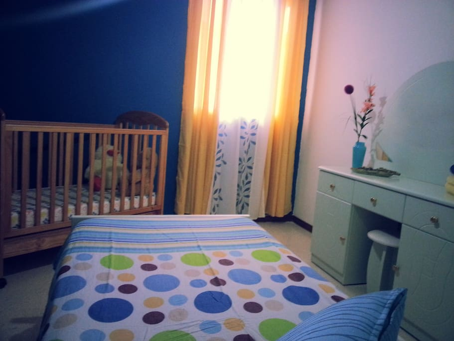Brightly lit bedroom with single bed and bed for toddler.