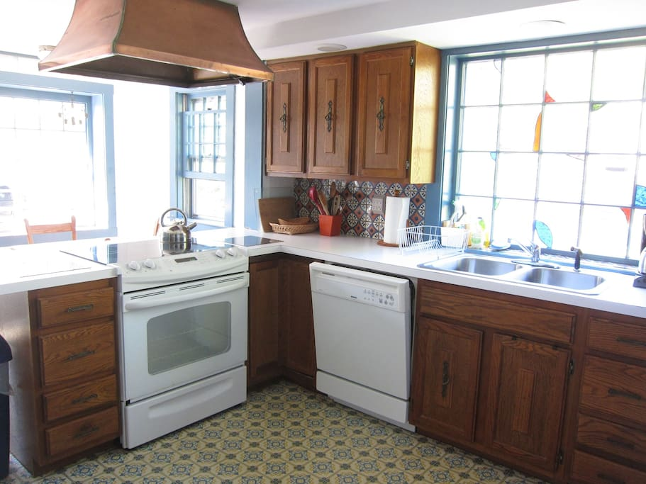 Five burner convection stove, large dishwasher, stained glass insets in windows