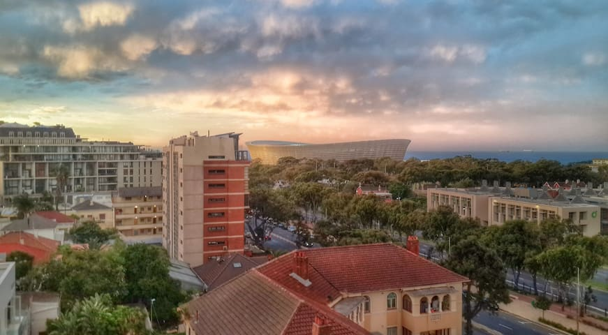 Views from balcony: Cape Town Stadium, the V&A Waterfront, Signal Hill, and sea.