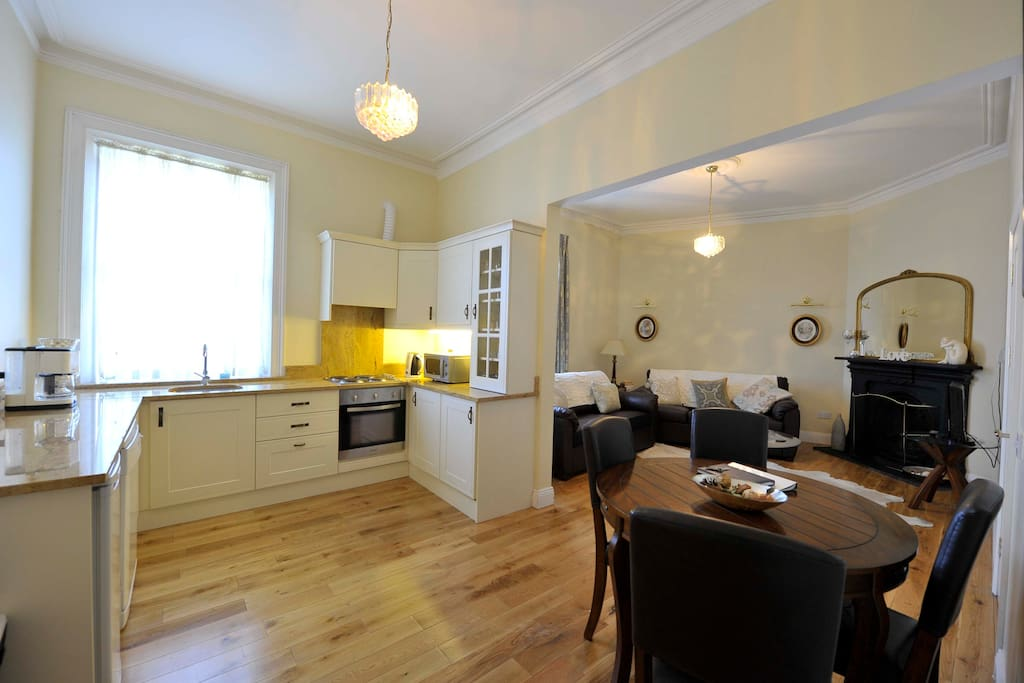Airy kitchen/living room with open fire and plenty of natural light.
