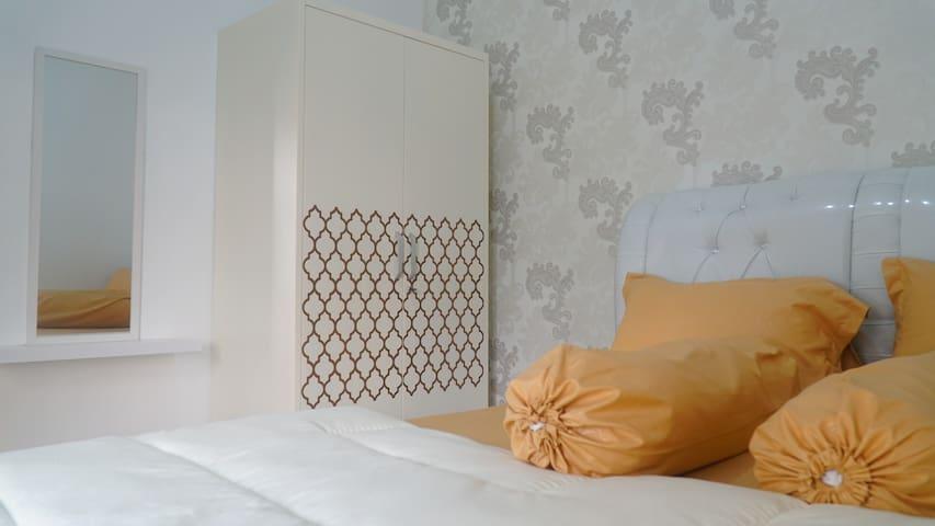 Kamar tidur lainnya di lantai atas yang terdiri dari tempat tidur ukuran queen, sprei, selimut, AC, lemari pakaian, gantungan baju, meja kecil, kursi puuk, cermin, gordyn dan lampu yang dapat dikondisikan menjadi lampu tidur.