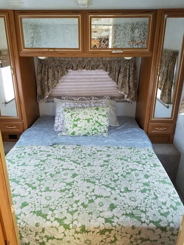 Queen bed in rear of RV. Room has a partition for privacy.