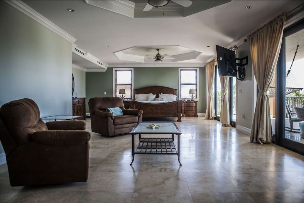 Open living space master bedroom with sitting area, large, flat screen TV and king size bed