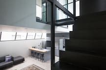 Stairs and high windows give a nice play of space and light.
