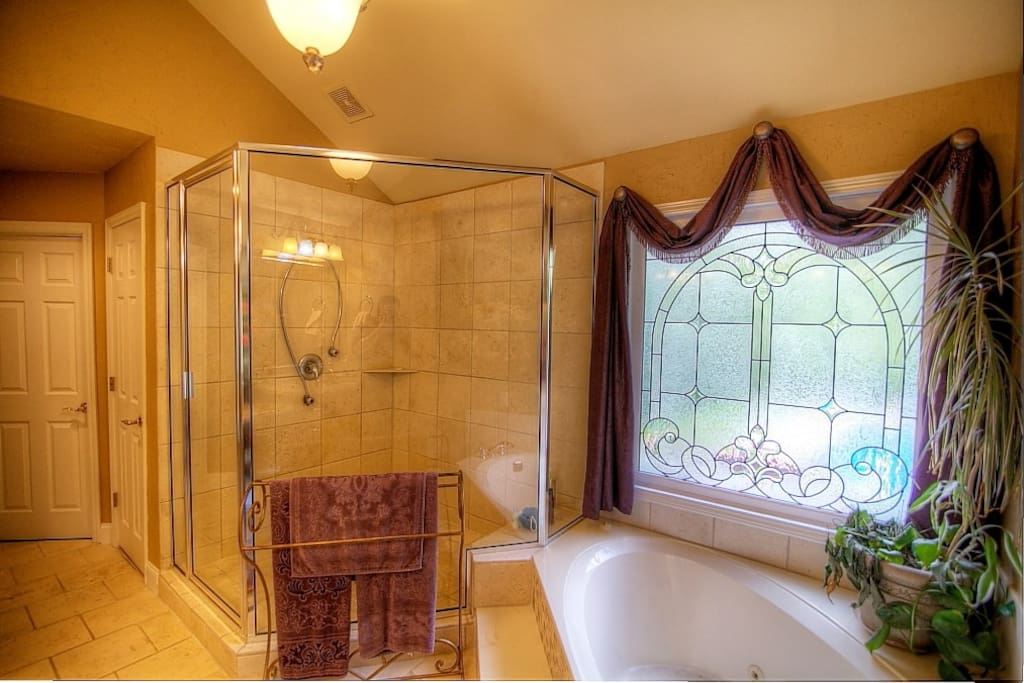 Master bedroom with a huge shower, body sprays and a bench for shaving.