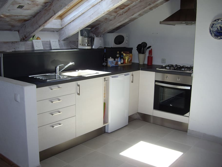 Newly fitted kitchen with gas hob and electric oven, microwave.