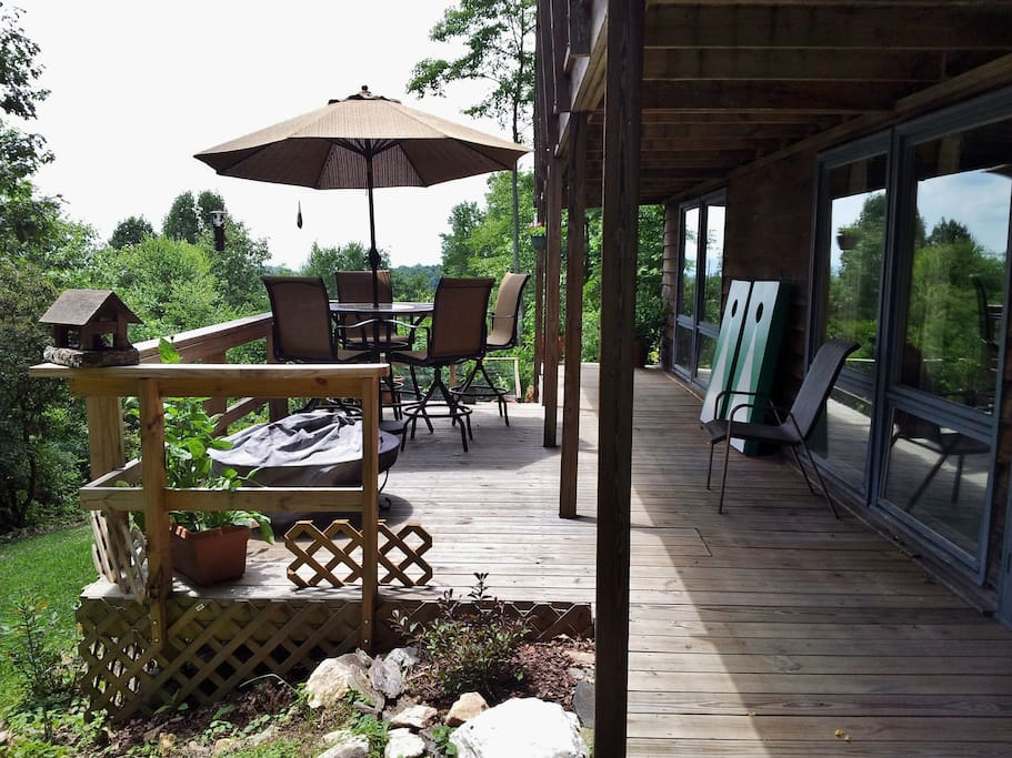 Downstairs deck with umbrella table for eating, bird watching, and relaxing. Also a cornhole game for enjoyment.