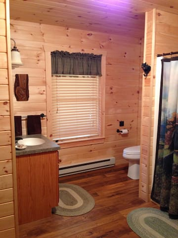 Large bathroom decorated in a black bear motif, oversize hot shower, plenty warm with the baseboard heater.  Door to the great room, or use the pocket door to the master bedroom.