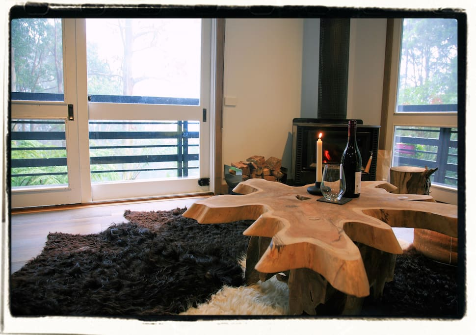 Timber tree trunk coffee table in front of a fire place.