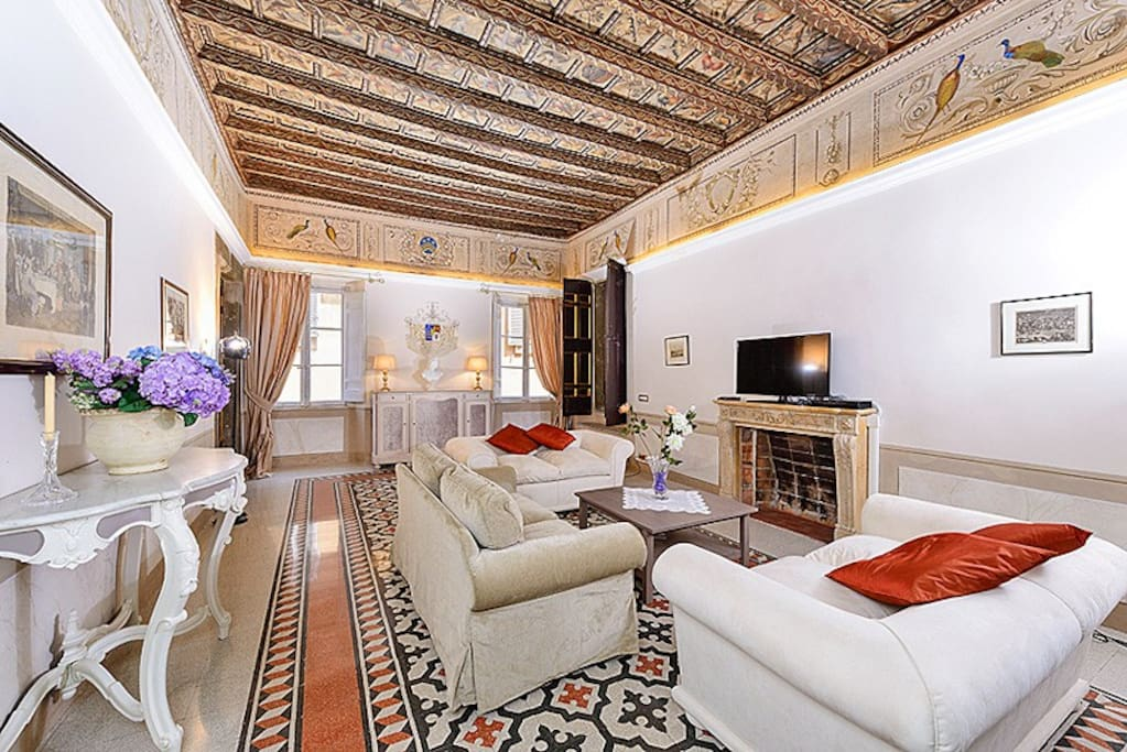 The wonderful sitting room, seen past the entry door. Notice the beautiful tiles, the high vault wood beam ceilings, with paintings, and the frescoes.