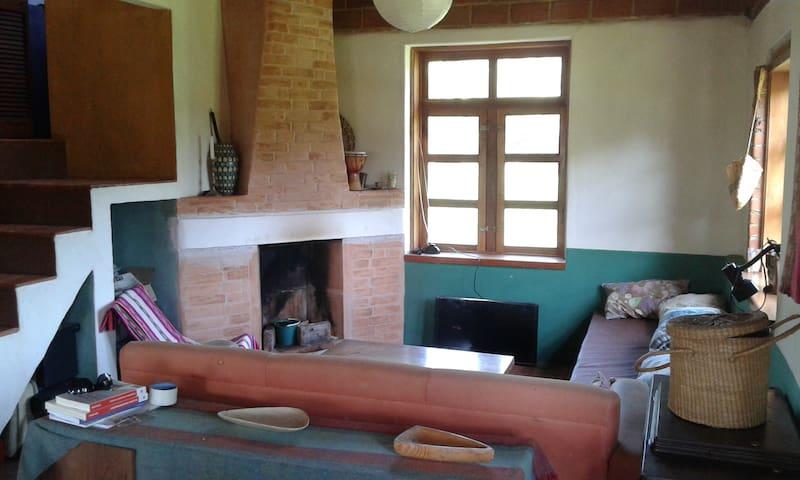 Sala espaciosa e iluminada con chimenea. Escalera al sanitario seco y a la segunda planta
