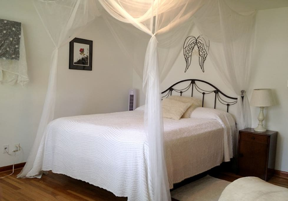 The white bedroom features a comfortable Queen pillow-top bed surrounded by romantic decor.