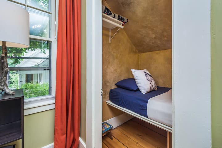 Twin bed with nightstand and reading light within the suite.