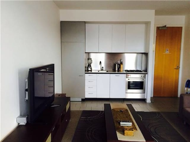 Kitchen with hidden bar fridge, dishwasher and microwave. All kitchenware included.