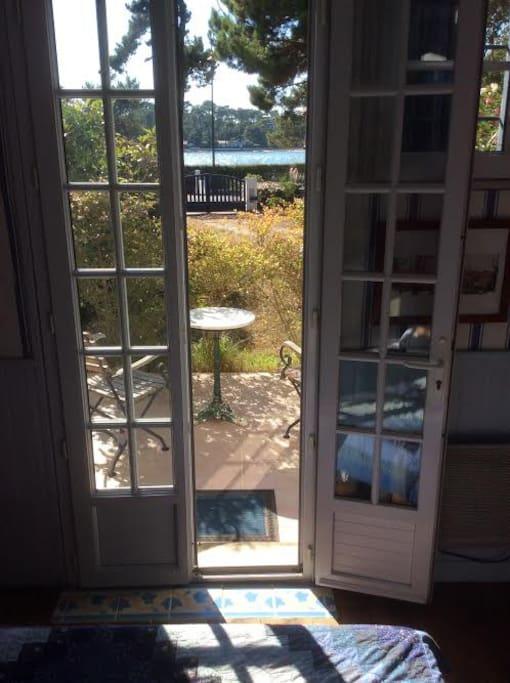 vue de la pièce à vivre (ou chambre Ouest) sur la terrasse et le lac au delà