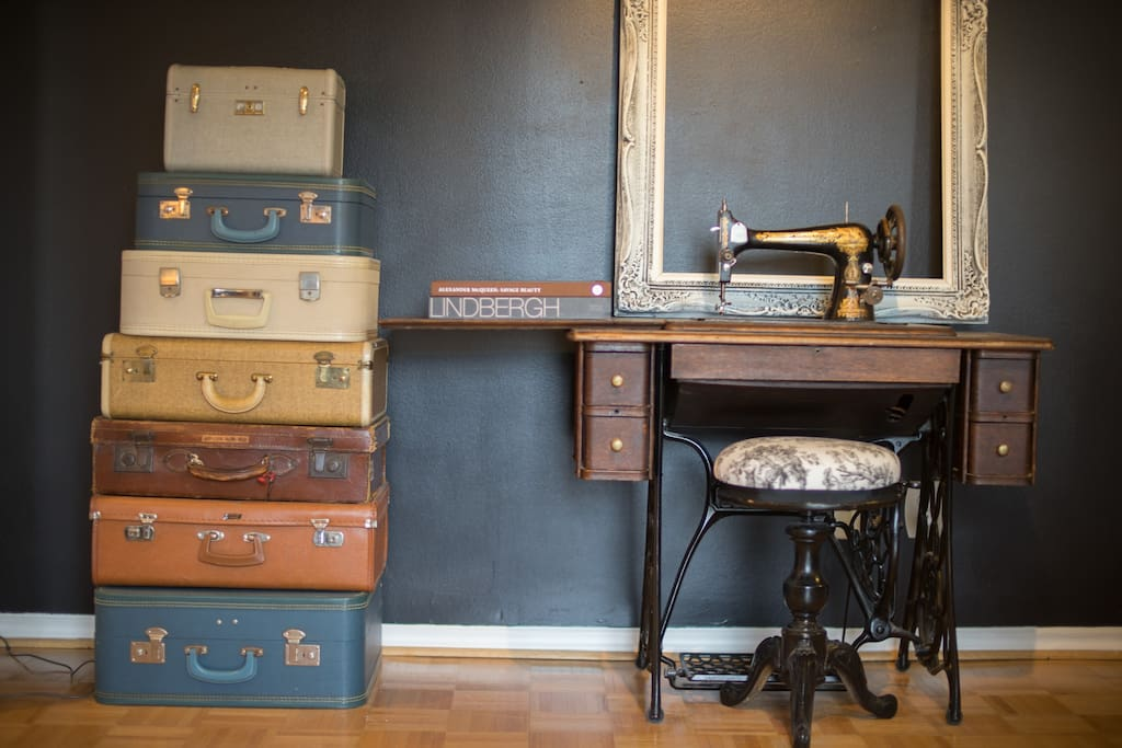 Living Room with vintage suitcases and antique sewing machine.  Entrance foyer is to the right.  Laundry to the left.