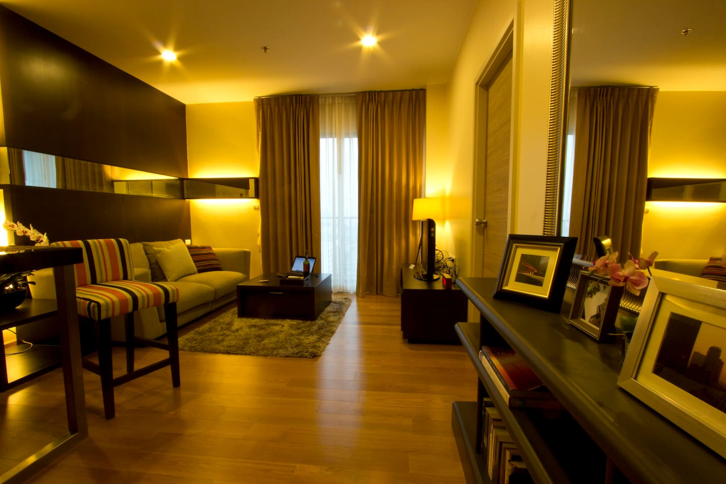 Contemporary modern living space, wood floor, fluffy carpet, large couch, warm atmosphere & lighting-very homey