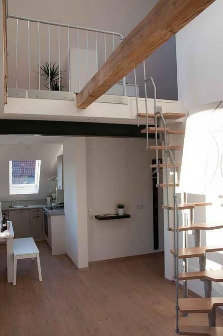 Blick aus dem Wohnzimmer in die Küche und die Treppe nach oben zum zweiten Schlafzimmer