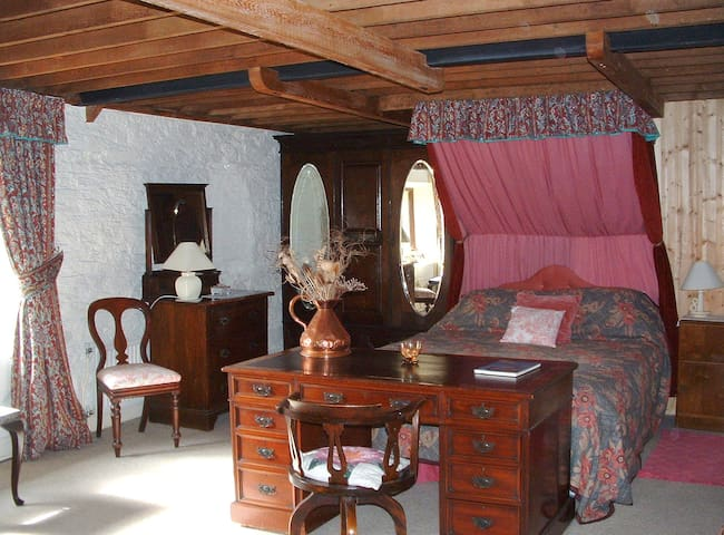 Upstairs canopied bed, in large bedroom with adjacent bathroom.