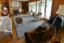 The living room area with floor-to-ceiling windows that face the water. (fireplace is not active)