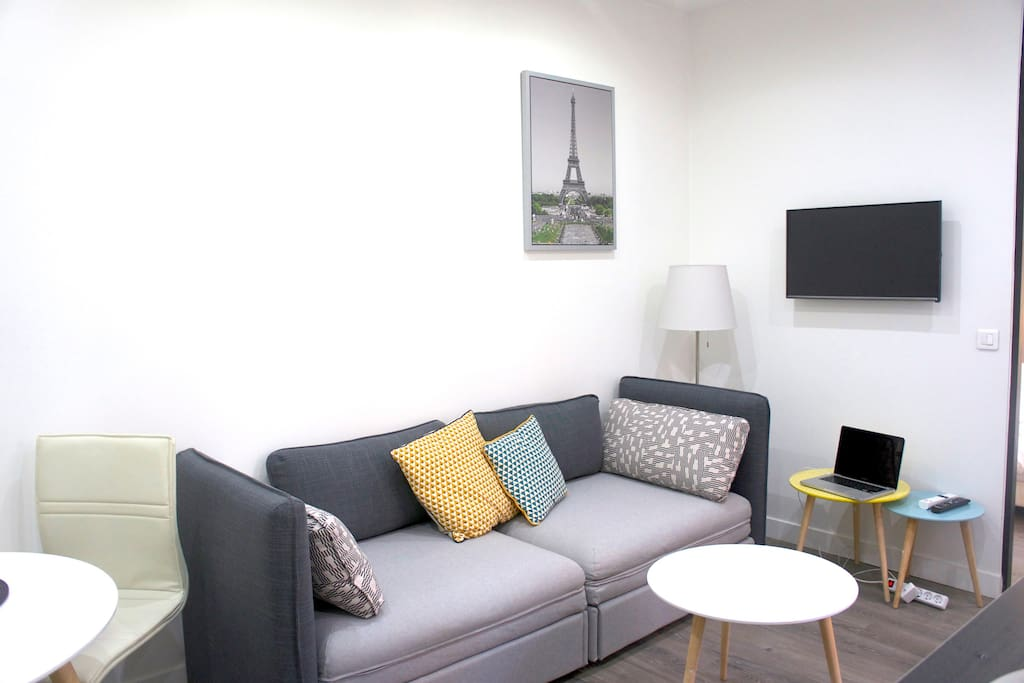Bright living room at daytime with a new Eiffel picture on the wall.