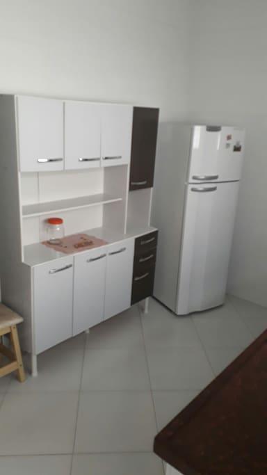 Cozinha com geladeira e armários