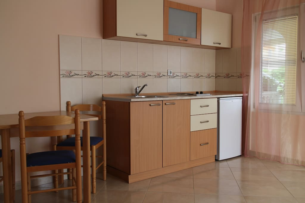 Each of three apartments spots a built-in kitchenette with a fridge and electric stove.