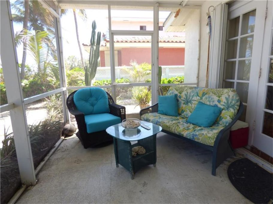 """Florida room"" - screened in patio porch with dining and living room area."