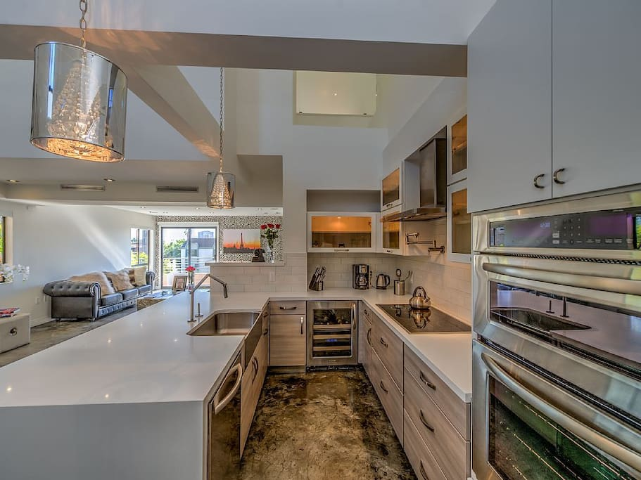 Chef's kitchen with quartz countertops and all amenities--wine cooler,dishwasher, stove, microwave, coffee maker, tea kettle, dishes, glassware, pots/pans, etc