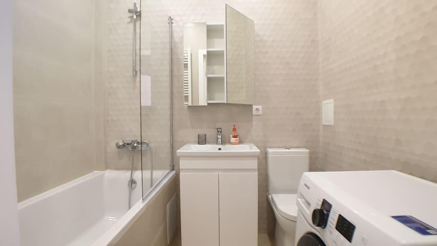 bath with shower, washing machine.
