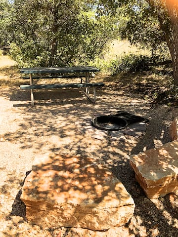 Each cabin has an outdoor fire place with a grill grate and picnic table.