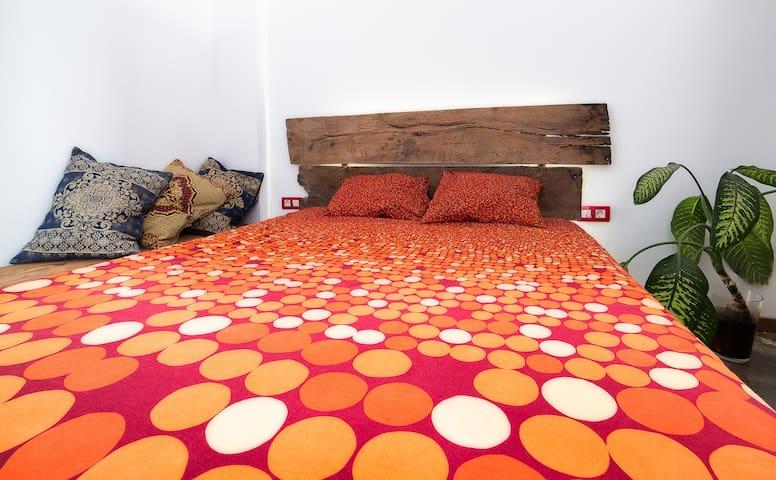 una cama confortable y con luminaria de led tras el cabecero de roble de orleáns