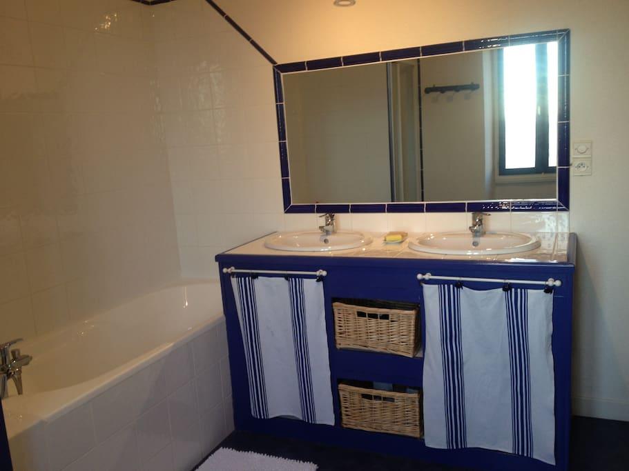 Une salle de bain avec double vasque, baignoire et douche