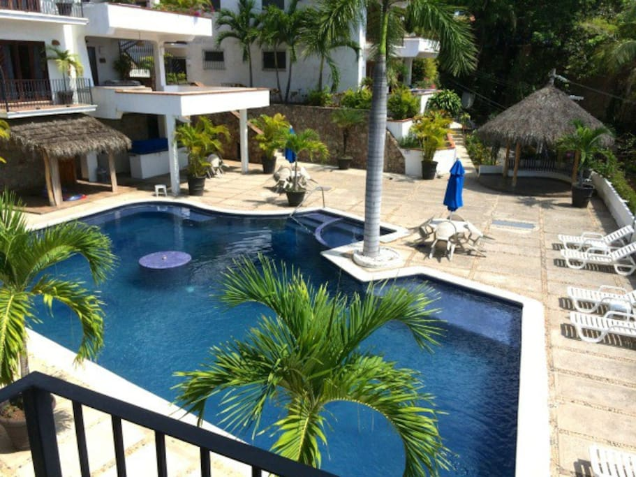Salt water pool with heated whirlpool, fountain, palapas, and outdoor bar