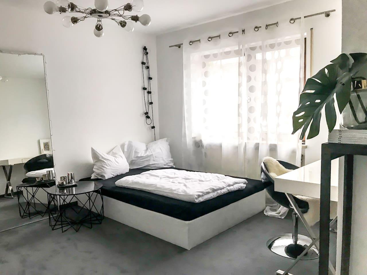 Schlafzimmer mit großem Bett und Arbeitsplatz