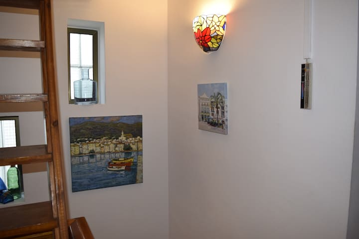 Art in the stairwell - original painting of nearby beach town Cadaqués