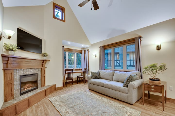 Living room with dining nook and fireplace. Sofa pulls out into a queen size bed.