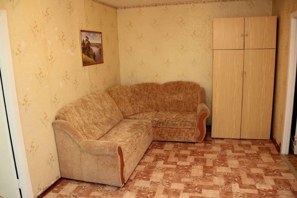 Двуспальный угловой диван в большой комнате