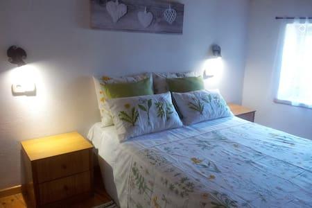 Habitación con cama doble en casa rústica. - Rumah