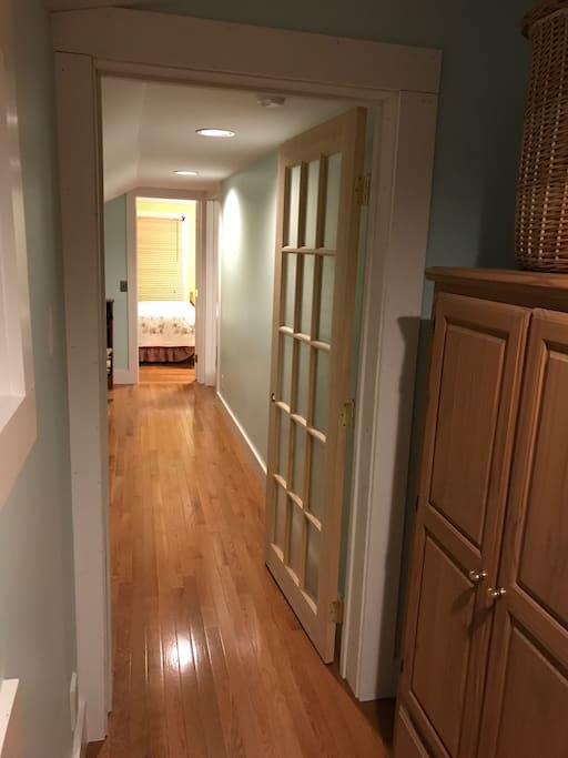 Two upstairs bedrooms with full-size beds are at the end of a private hallway which can accommodate a twin cot for another guest.