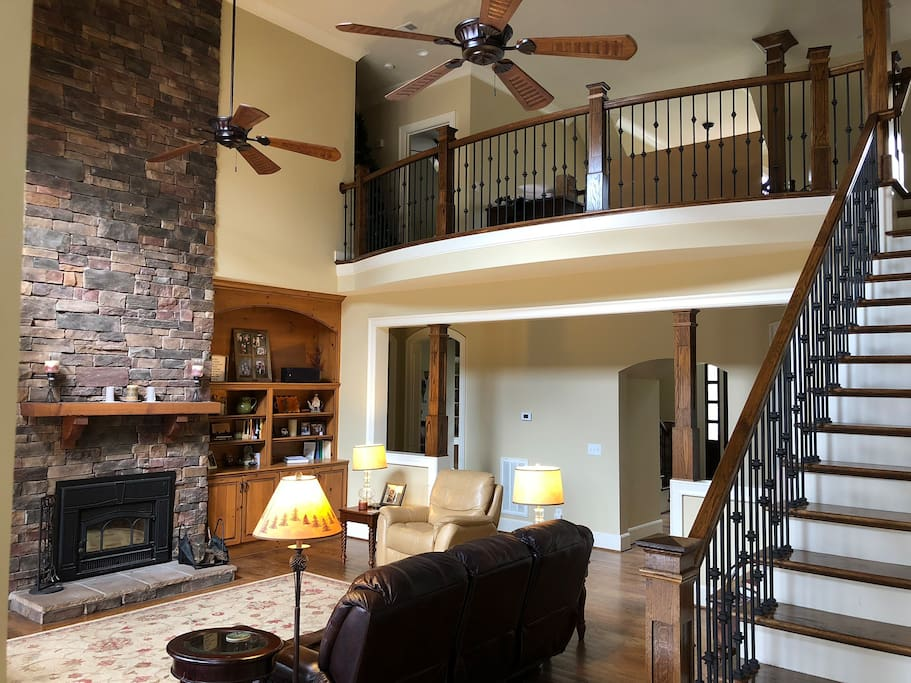 "Two story den with stone fireplace, comfortable seating and 50"" 4K HDTV"