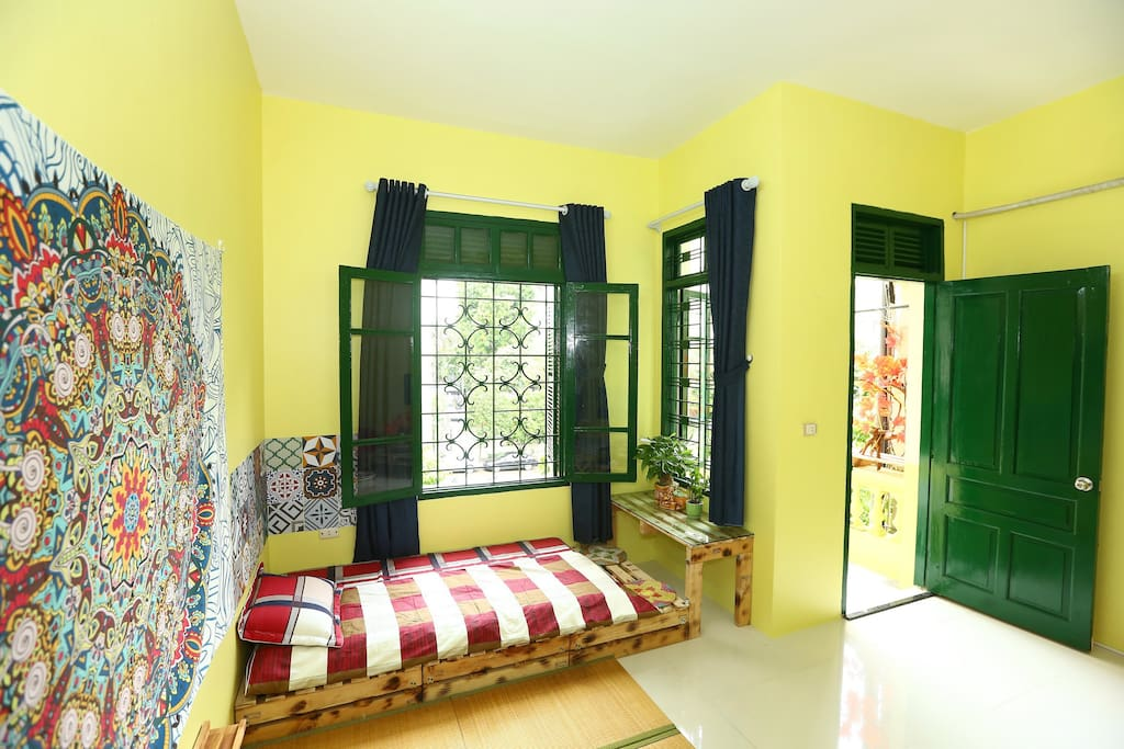 The yellow bed rooms. There are a double bed and a single bed in this room. There is also a private balcony from which you can look to the road. Two windows to welcome sunlight and fresh air.
