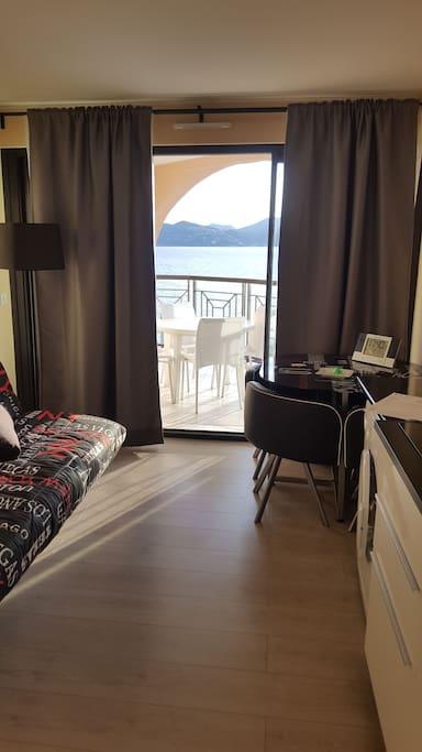 Cuisine - salon avec canapé - lit supplémentaire et terrasse vue mer