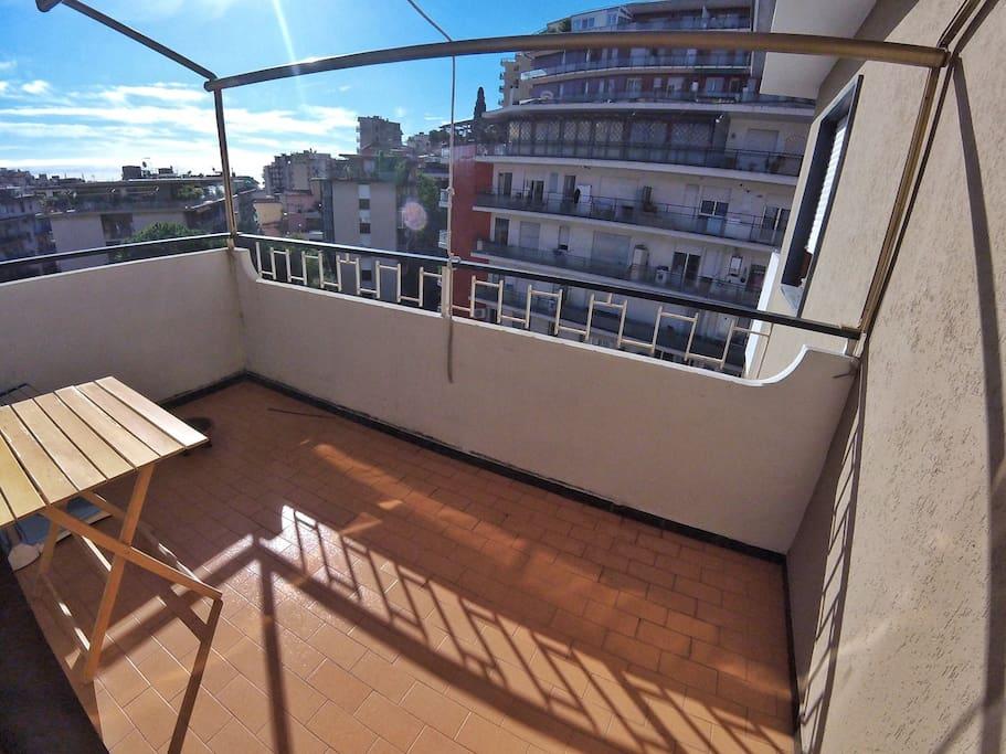 Terrazzo vivibile con tenda e tavolo con 4 sedie