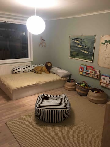 Kids room with lots of toys to play with and a queen size bed