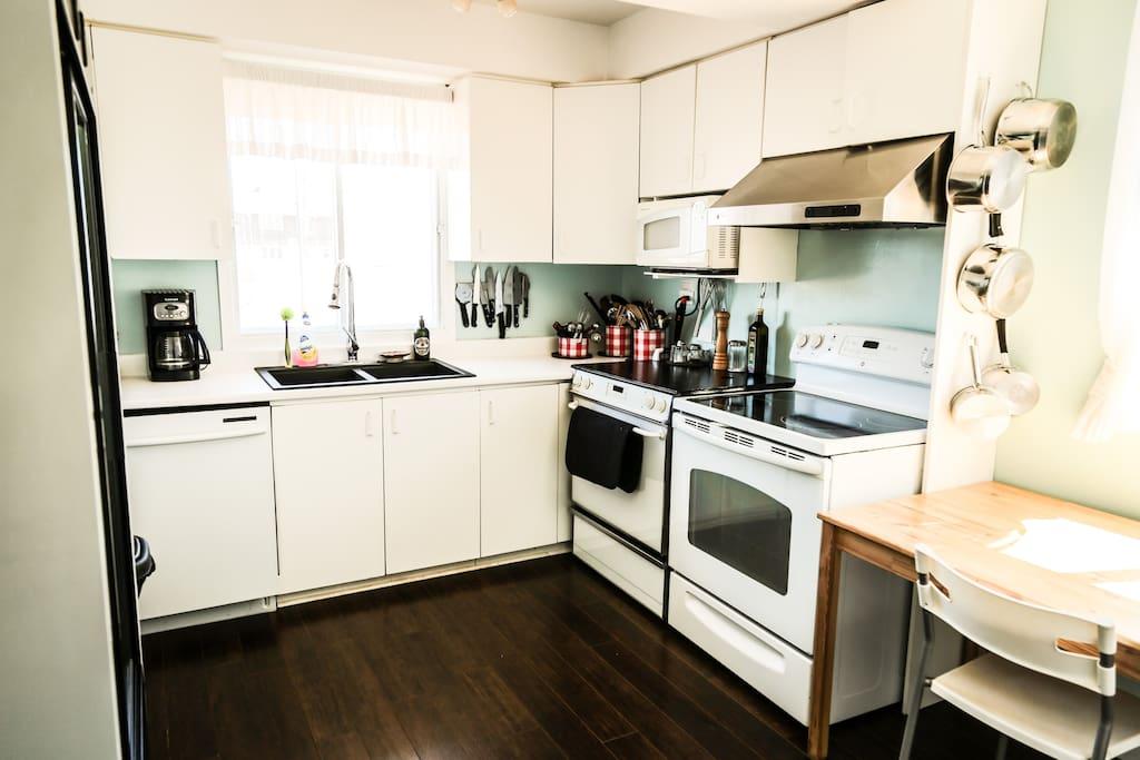 Une grande cuisine commune : deux poêle, un réfrigérateur vitré double, une multitude d'accessoire de cuisine et de vaisselle, et beaucoup, beaucoup de rangement!