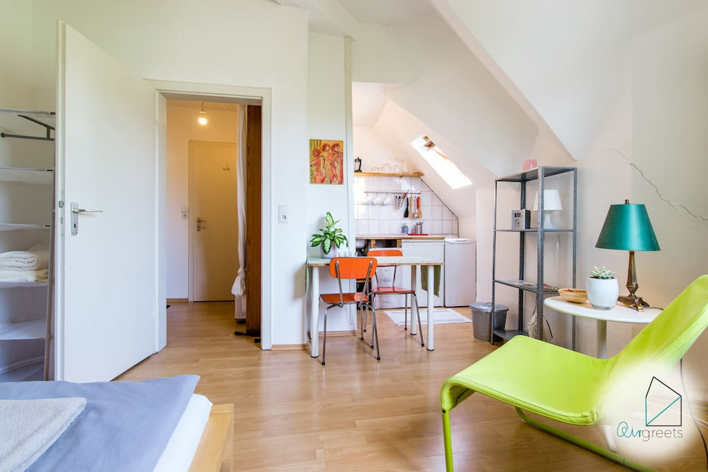 The studio apartment includes a sleeping area and a kitchen with a dining table.