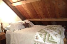 Full Bed with night stand in upstairs sleeping loft.