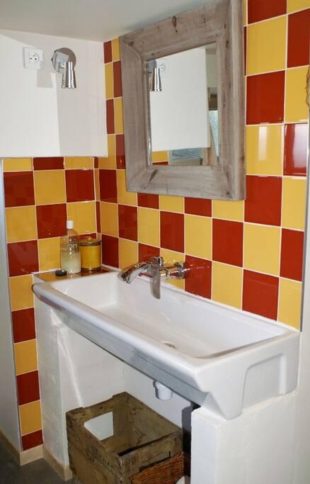 Salle de bain  avec baignoire et  lave linge sèchant